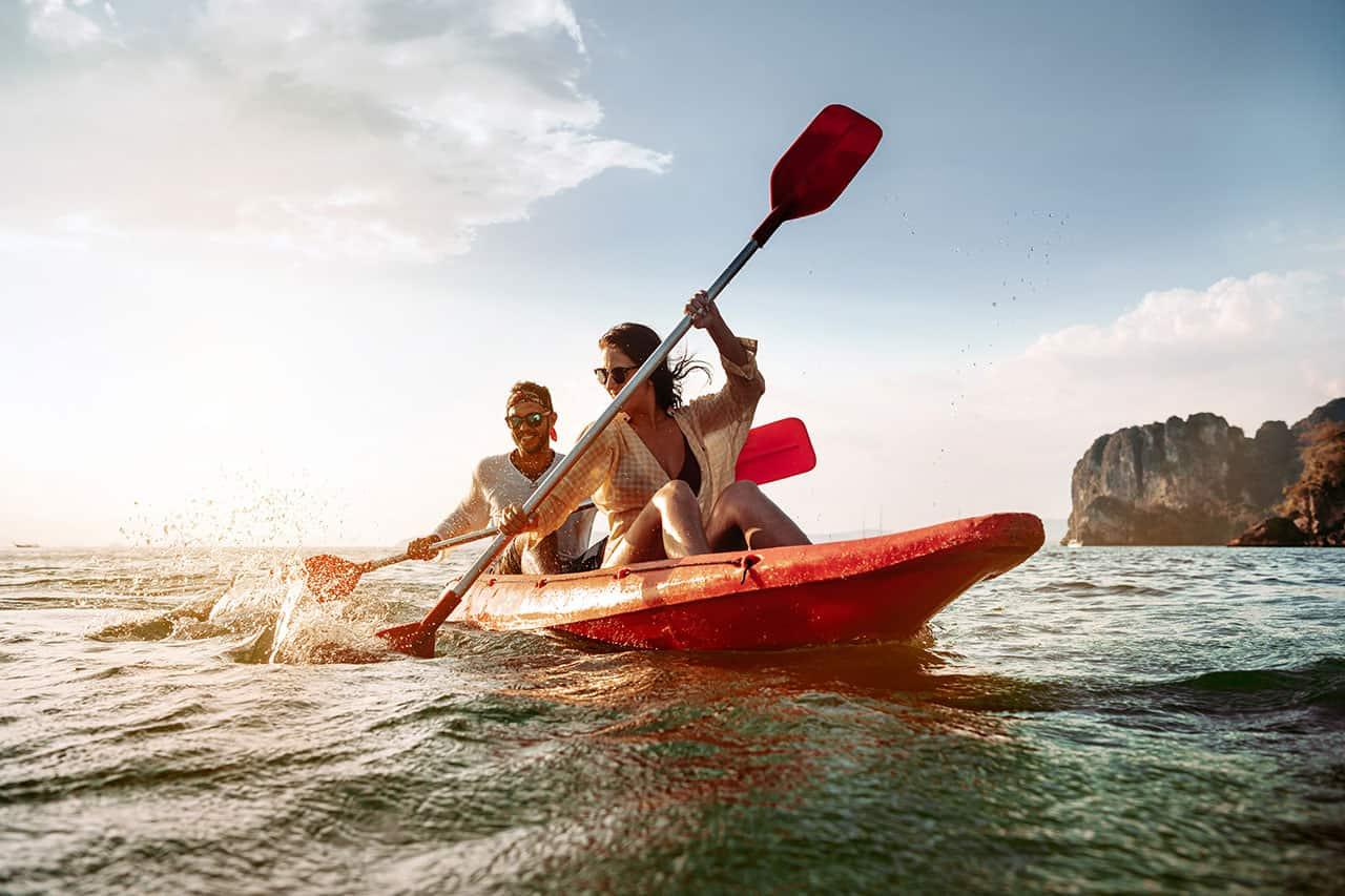 Iloiselta näyttävä pariskunta melomassa kajakilla tai kanootilla ulkomaanlomalla.