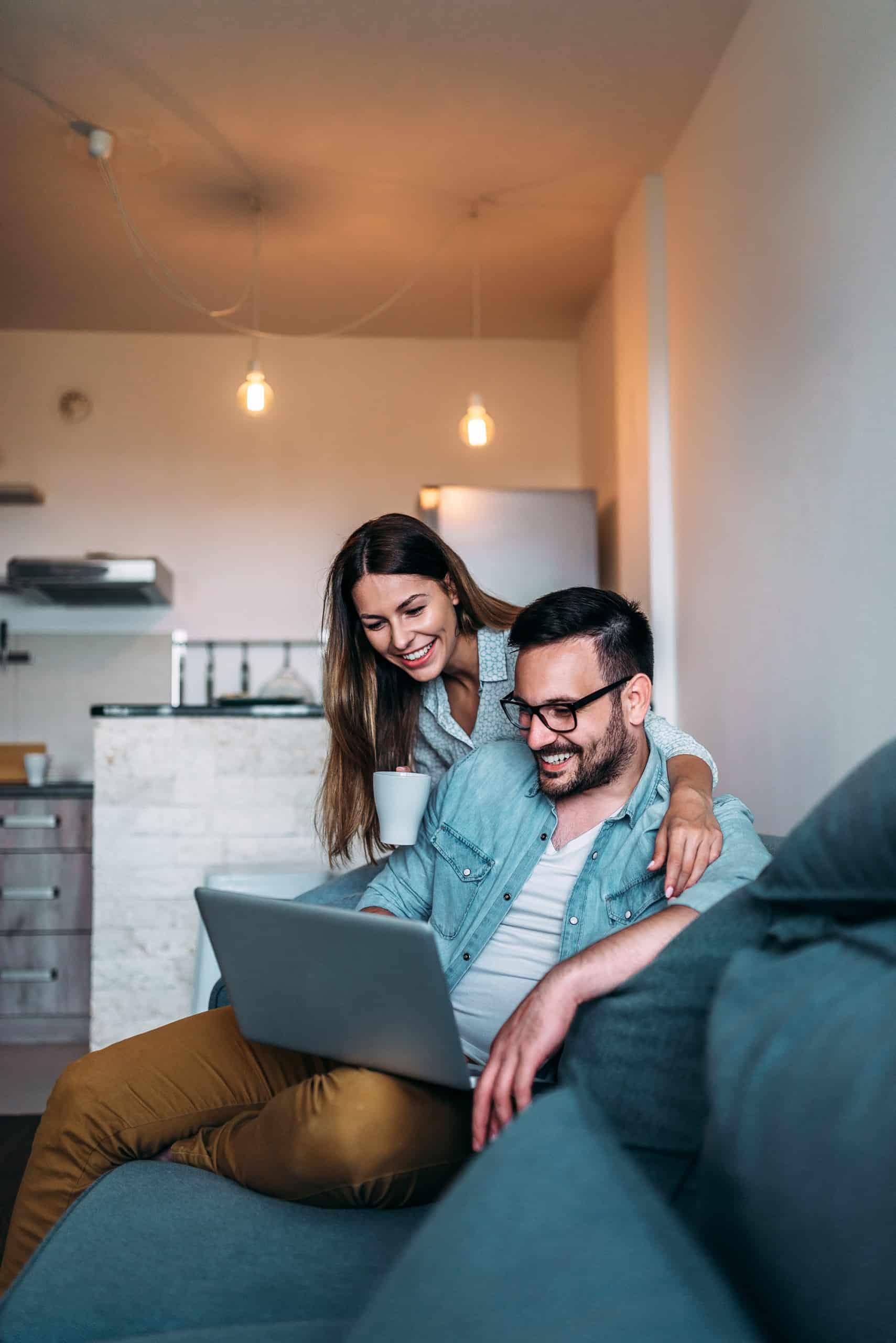 Pariskunta käyttää kannettavaa tietokonetta istuessaan sohvalla.